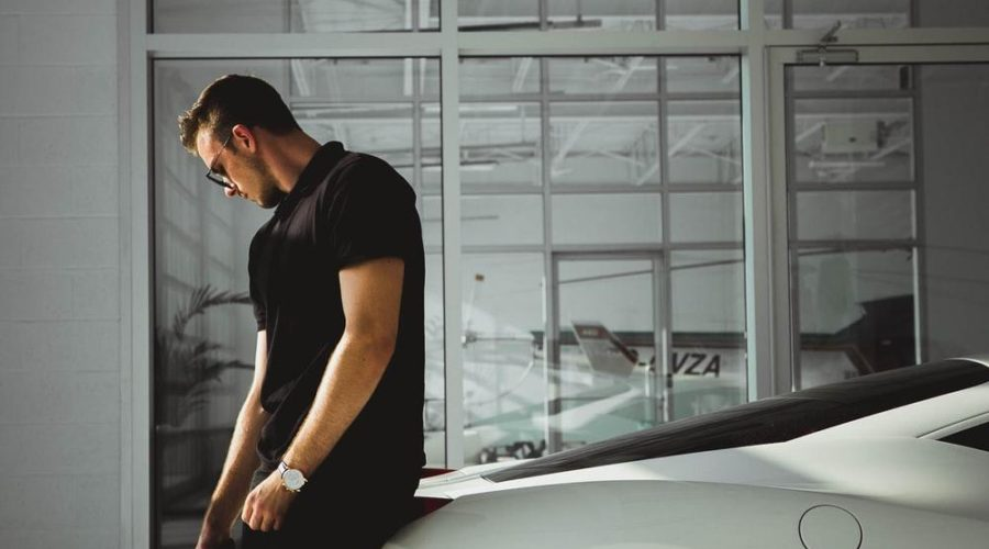 man sitting on car near glass window